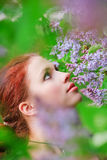 Young Girl Smelling Flowers Stock Images