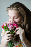 Young girl smelling flowers. Young girls with flovers,  beautiful smile and eyes Stock Images
