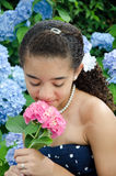 Young girl smelling pink flower Stock Photo
