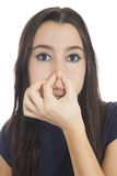 Young girl smelling something stinks. Close-up of a woman holding her nose isolated on white Background Stock Photos