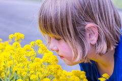 Young girl smelling yellow flowers Stock Photo