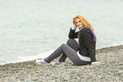 Young girl with a smile sits on pebble beach by the sea on a cloudy cold day Royalty Free Stock Photo