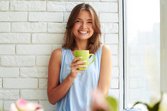 Young girl smiled sunnily while enjoying a cup of coffee in the Royalty Free Stock Photo