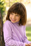 Young Girl Smiles. An adorable young Hispanic American girl in the 5-8 year old range. She is wearing a pink purple turtleneck shirt, leans against a tree and Stock Image