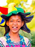 Young girl smiling with colorful clown hat and funny glasses. Young girl smiles with colorful and very funny hat and with glasses with written boom Stock Photography