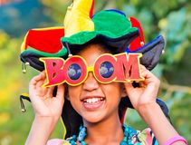 Young girl smiling with colorful clown hat and funny glasses. Young girl smiles with colorful and very funny hat and with glasses with written boom Stock Photo