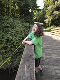 Young Girl Smiles while Fishing off Bridge Royalty Free Stock Photo