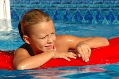 Young Girl Smiles on Float Toy in Pool. Young blond girl smiles on a red float in a brilliant blue swimming pool Royalty Free Stock Images