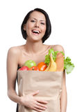 Young girl smiles handing the packet of greens royalty free stock photography