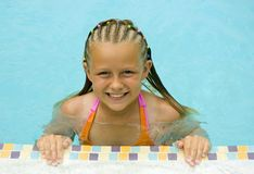 Young Girl Smiles at Poolside. Young girl with braided hair smiles at edge of swimming pool Royalty Free Stock Images