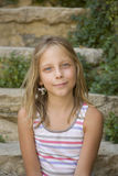 Young girl smiles sitting on an outdoor steps Stock Images