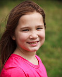 Young girl smiling. A young girl in a pink short with big smile on a windy day Stock Photos