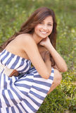 Young girl smiling. A portrait of a young teenage girl smiling in a dress in field royalty free stock image