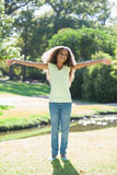 Young girl smiling with arms outstretched in the park Stock Photos