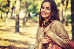 Young  girl smiling in autumn scenery. Stock Photo