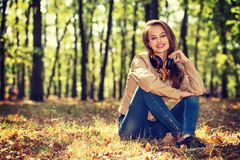 Young  girl smiling in autumn scenery. Royalty Free Stock Photography