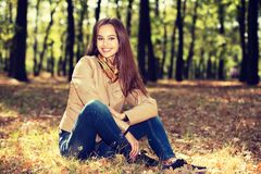 Young  girl smiling in autumn scenery. Stock Images