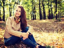 Young  girl smiling in autumn scenery. Stock Image