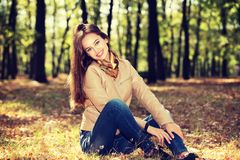 Young  girl smiling in autumn scenery. Royalty Free Stock Image