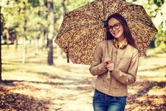 Young  girl smiling in autumn with umbrella Royalty Free Stock Images
