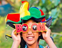 Young girl smiling with colorful clown hat and funny glasses. Young girl smiles with colorful and very funny hat and with glasses with written boom Royalty Free Stock Photography