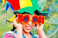 Young girl smiling with colorful clown hat and funny glasses. Young girl smiles with colorful and very funny hat and with glasses with written boom Stock Photos