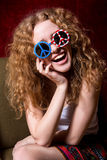 Young girl smiling with curly hair wearing sunglasses with the A Stock Photo