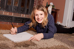 Young girl smiling and drawing. Young girl lying on home floor smiling while drawing pictures Royalty Free Stock Image