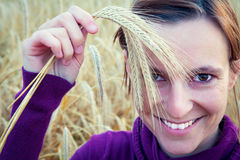 Young girl smiling with ear in her hand, on a wheet field Stock Images