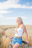 Young girl is smiling in the field with retro bike Stock Images