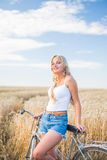 Young girl is smiling in the field with retro bike Stock Image