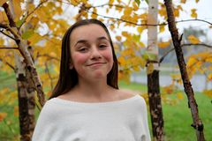Young girl smiling in a forrest of birch trees royalty free stock image