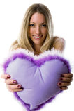 Young girl smiling holding out a Violet heart Royalty Free Stock Photo
