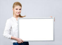 Young girl smiling and holding a white blank board Royalty Free Stock Images