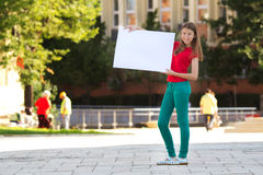 Young girl smiling and holding a white cardboard Stock Photo