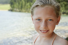 Young Girl Smiling By Lake Stock Photo