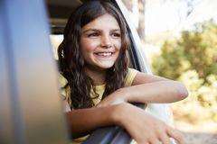 Young girl smiling and looking out of open car window Royalty Free Stock Images