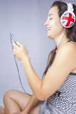 Young girl smiling with phone and headphones. Of England stock photo