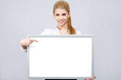 Young girl smiling and pointing to a white blank board. Royalty Free Stock Images