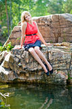 Young girl smiling on the rocks. Portrait of a young blonde girl in red sitting on the rocks and smiling Stock Image