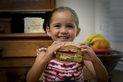 Young girl smiling with sandwich in hand stock photo