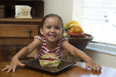 Young girl smiling with sandwich on table royalty free stock image