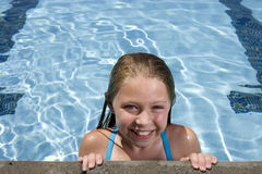 Young girl smiling by side of swimming pool Royalty Free Stock Photo