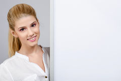 Young girl smiling and standing near a white blank board. Royalty Free Stock Photos
