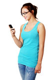 Young girl smiling to mobile phone. Stock Photos