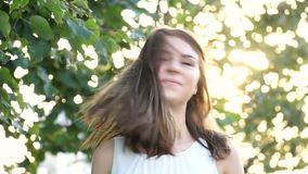 Young girl smiling twists head and her hair fly away in slow motion stock video