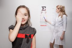 Optician. Young girl smiling while undergoing eye test Royalty Free Stock Photos