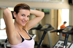Young girl Smiling while working out at the gym Stock Image