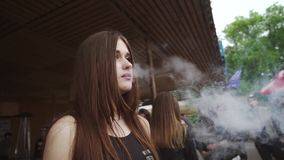 Young girl smoke electronic cigarette on street. Vaper festival. Crowd of people. Steam. Slow motion stock footage