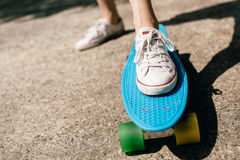 Young girl in sneakers on skateboard. Royalty Free Stock Image